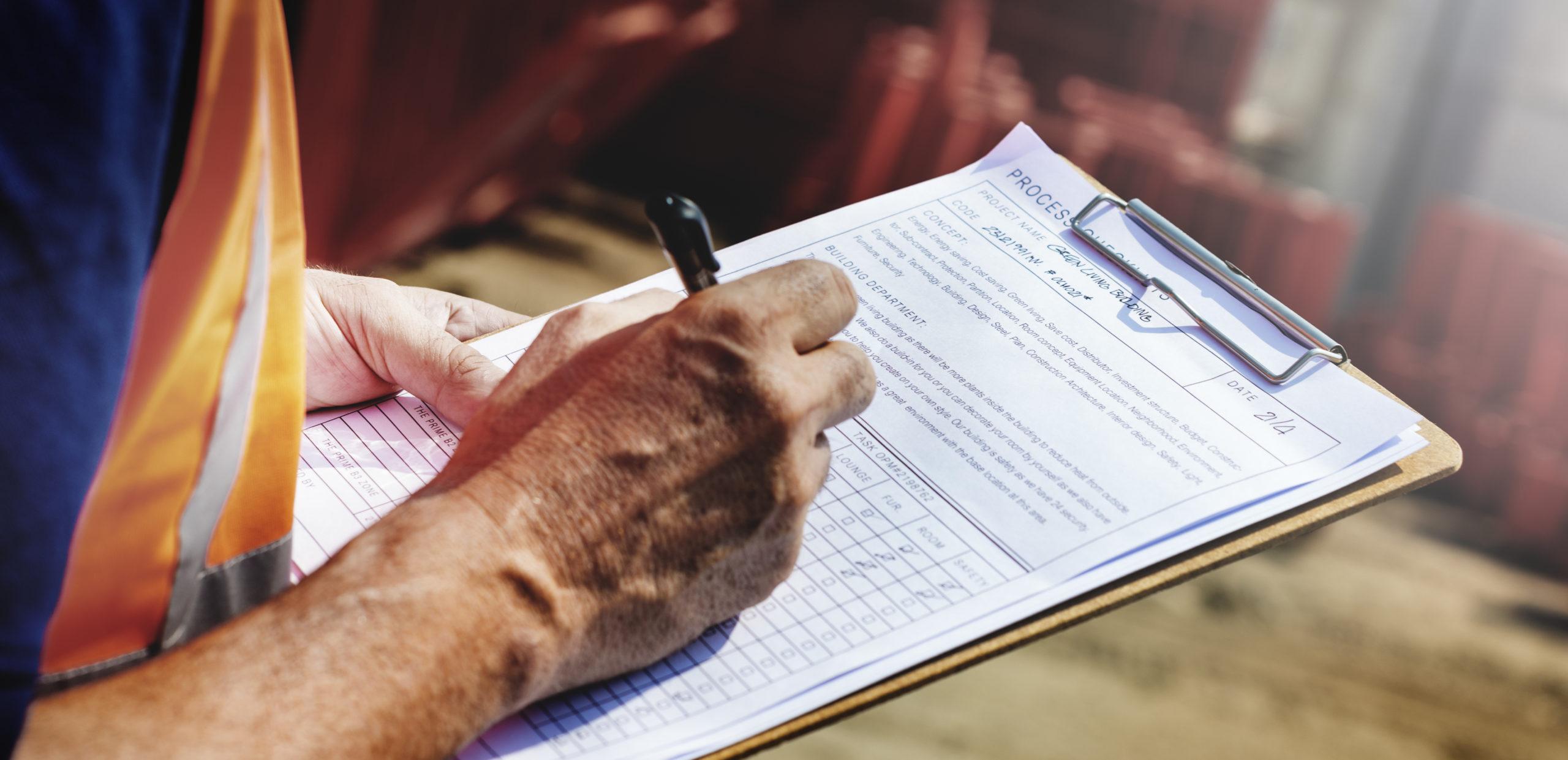 Bauarbeiter schreibt auf ein Klemmbrett